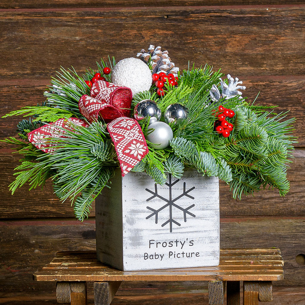 Centerpiece with pine cones, red berries, silver and frosty balls with red and white patterned bow in rustic white container
