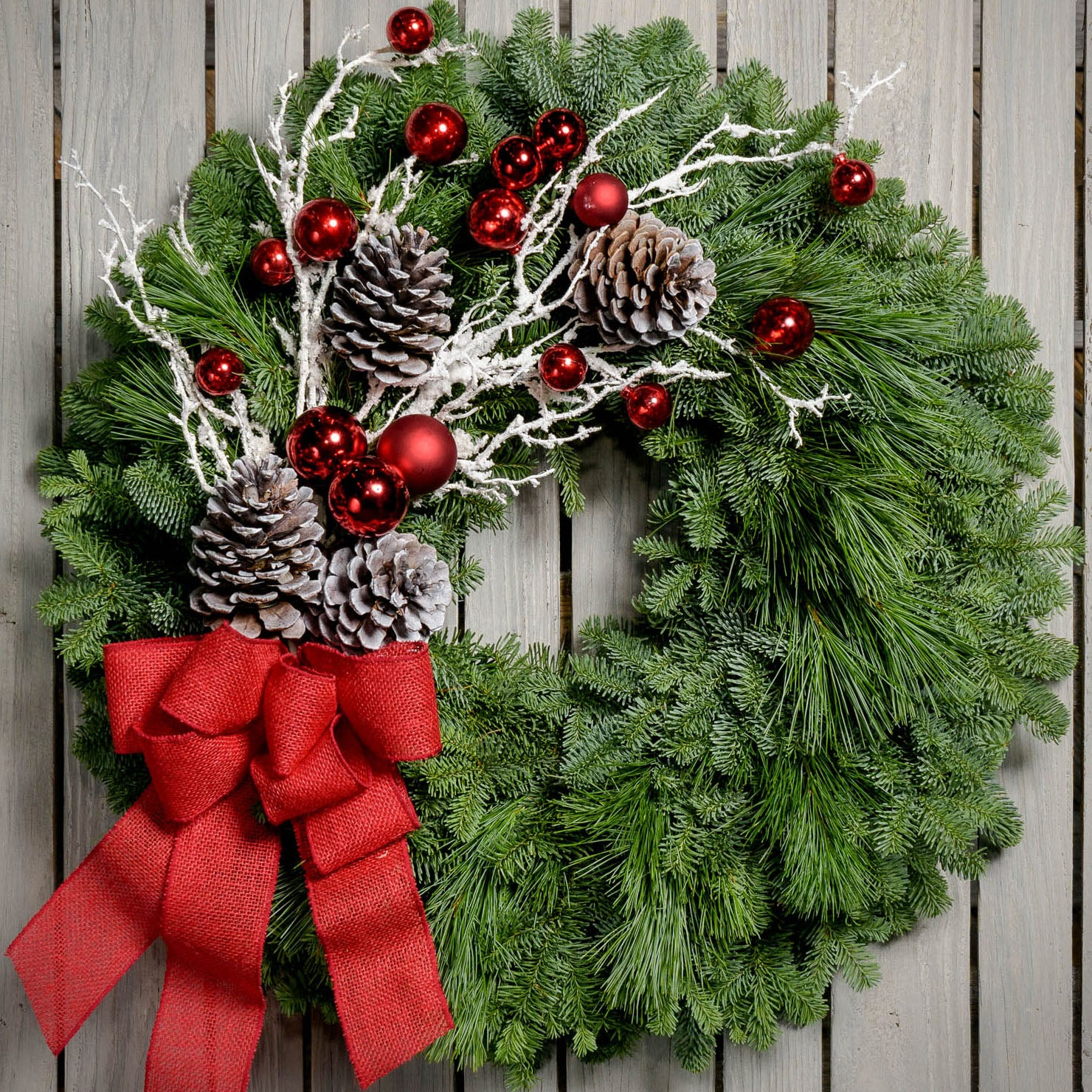 Christmas wreath made with noble fir, pine, pine cones, snow-covered branches, red balls and a red burlap bow close up
