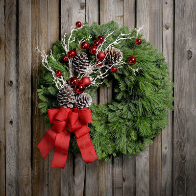 Christmas wreath with pine cones, snow-covered branches, red balls and a red burlap bow on a wooden plank background