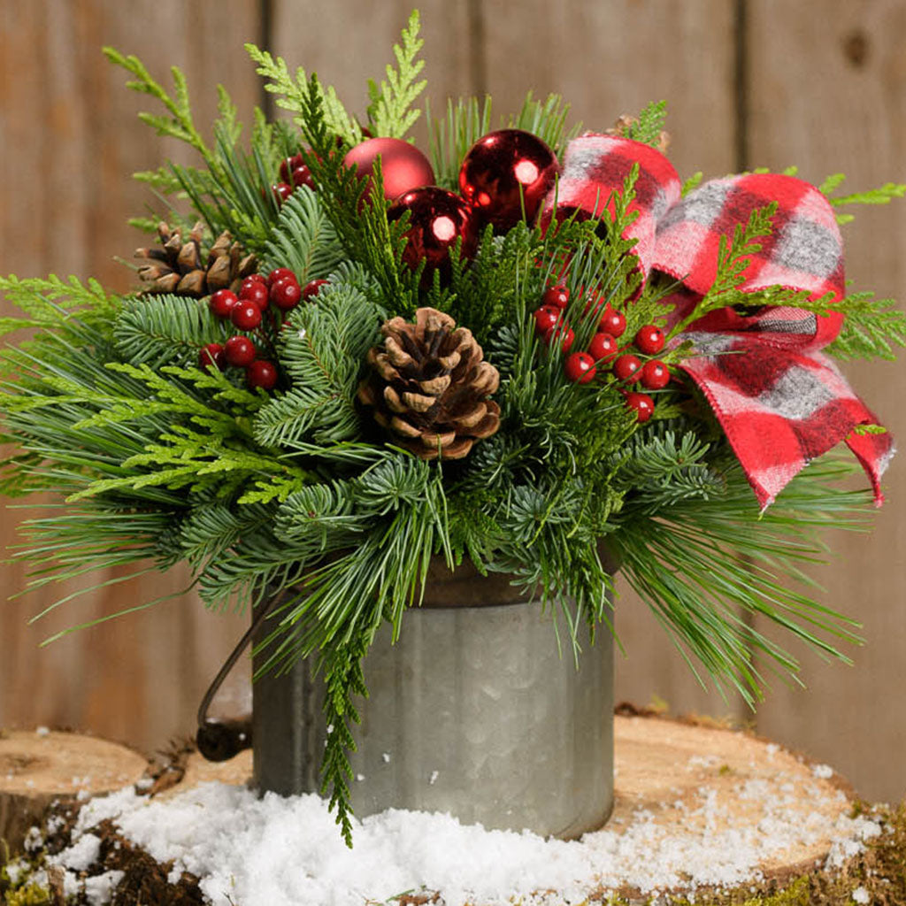 Evergreen centerpiece in a rustic,galvanized pail with a handle. Red berries,pine cones,red ball-ornaments & red plaid bow.