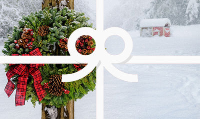 Country Christmas wreath on wooden post in snow