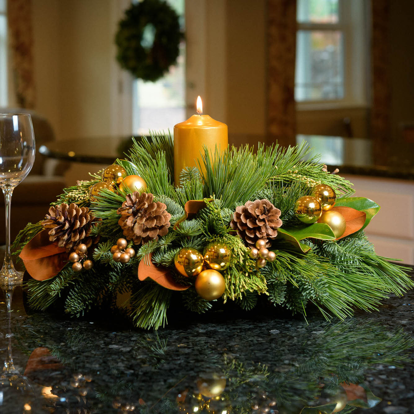 Golden magnolia centerpiece with pine cones, magnolia, gold balls and berries and a golden pillar candle on kitchen counter