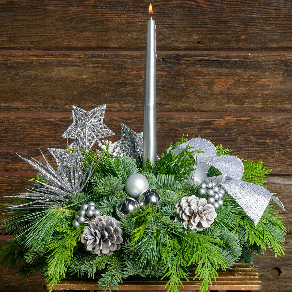 Evergreen centerpiece with Silver stars,berries, glitter bursts, ball ornaments & pine cones adorn a fresh base of greens