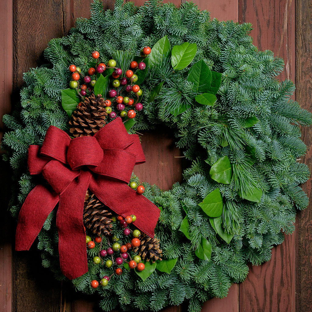 Holiday wreath with pine cones, faux autumn berries and a red linen bow on a base of noble, pine and salal greens