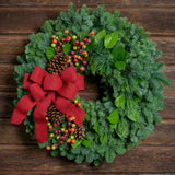 Holiday wreath with pine cones, faux autumn berries and a red linen bow on a base of noble, pine and salal greens on dark wood background