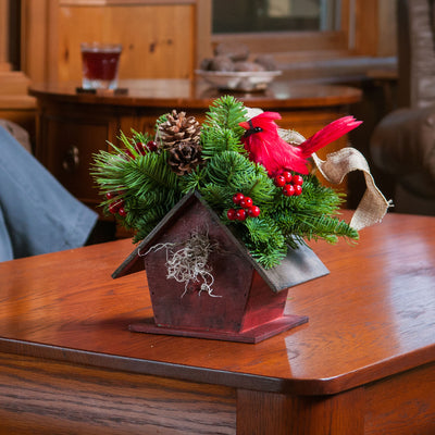 Holiday Rustic red birdhouse centerpiece with a cardinal, pine cones and a burlap bow on a coffee table