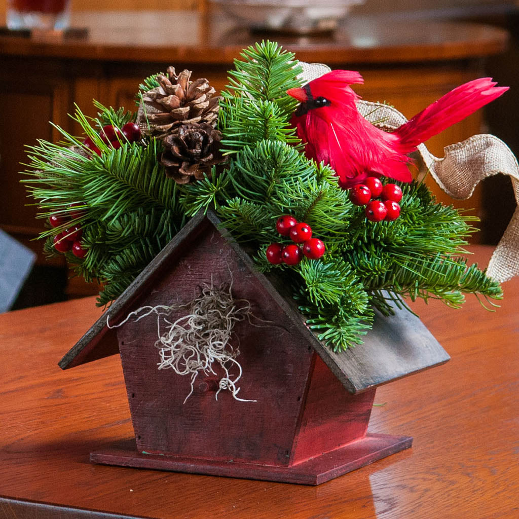 Holiday Rustic red birdhouse centerpiece with a cardinal, pine cones and a burlap bow close up