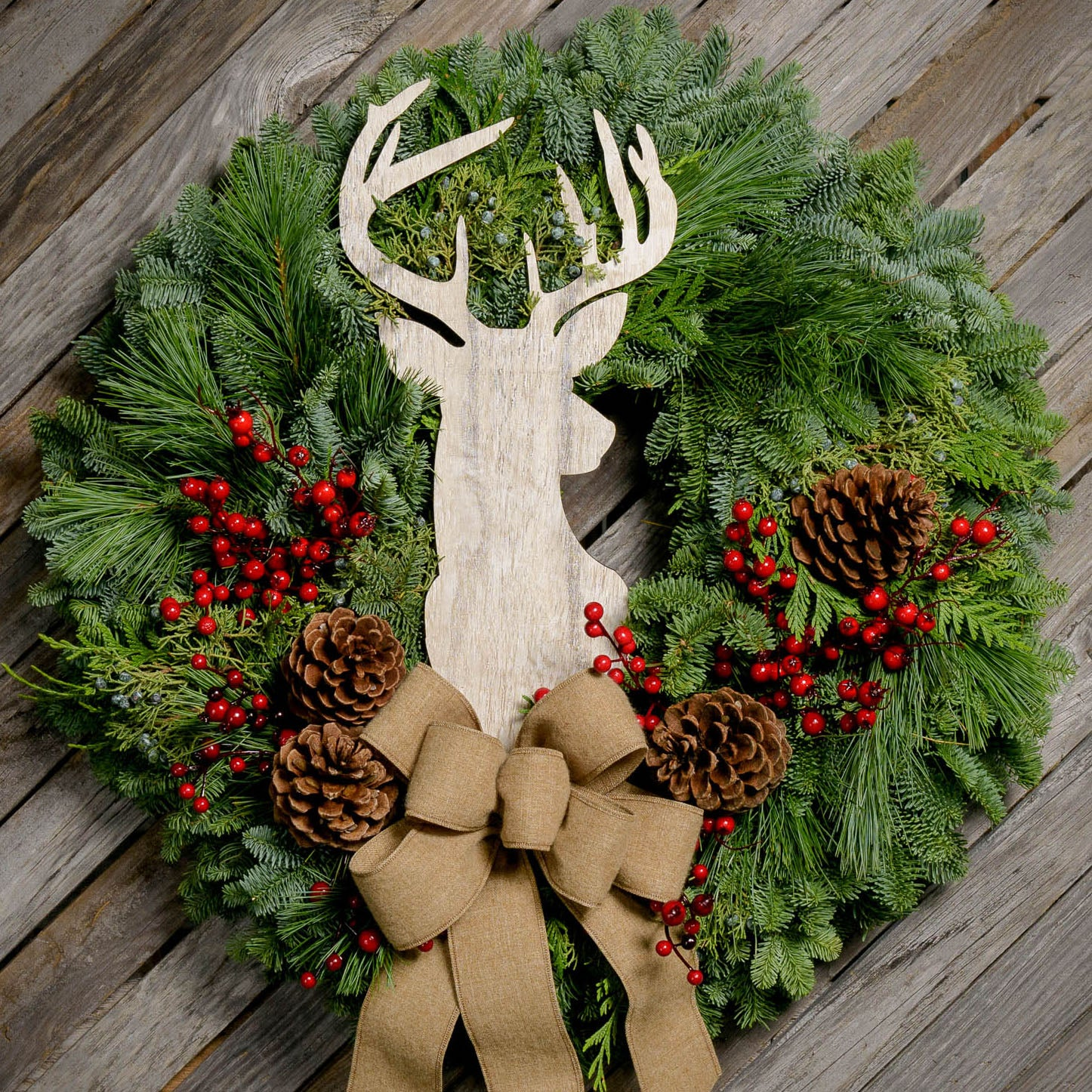 Fresh Evergreen wreath with pine cones, red berries, whitewashed stag head and natural linen bow close up