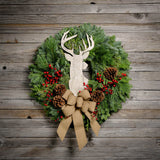 Fresh Evergreen wreath with pine cones, red berries, whitewashed stag head and natural linen bow on wooden plank background