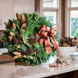 Fresh Evergreen wreath with magnolia, bay leaves, pine cones, berry clusters and a shimmery gold-red bow on kitchen counter