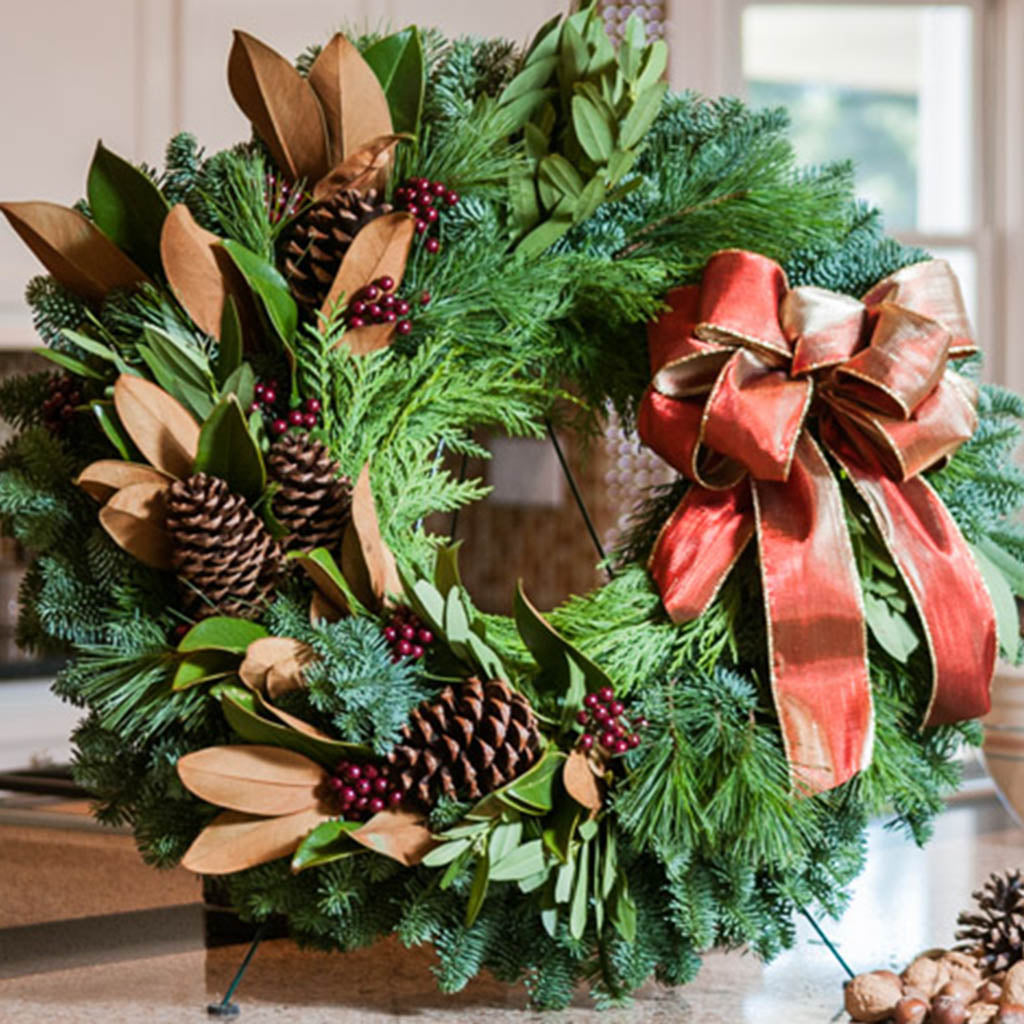 Fresh Evergreen wreath with magnolia, bay leaves, pine cones, berry clusters and a shimmery gold-red bow close up