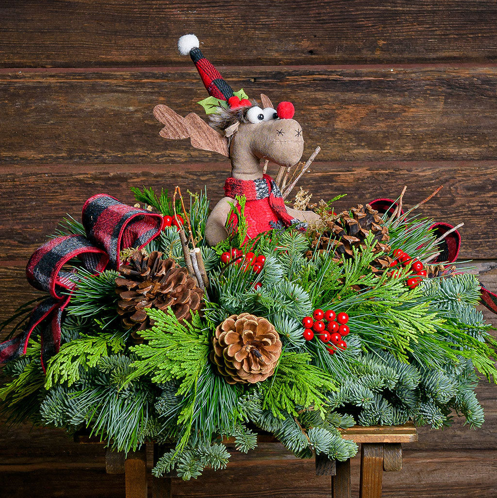 Fun Christmas centerpiece with pine cones, red berries and a red and white striped bow topped with a plush moose