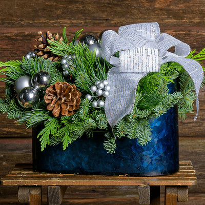 Centerpiece with pine cones,silver ball & berry clusters,midnight blue metal container & a white bow with silver glitter stripes