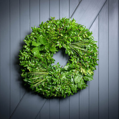 Hand picked fresh salal, green huckleberry and beargrass wreath on wooden background