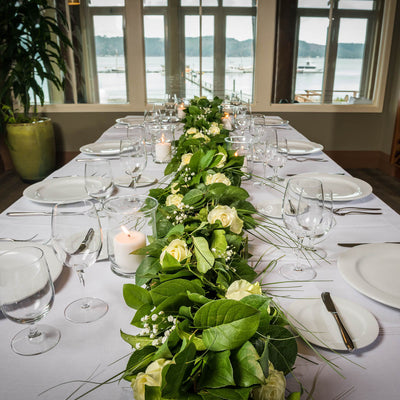 Hand picked fresh salal and beargrass garland on table with flowers