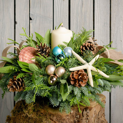 Fresh centerpiece with seashells, sea star, aqua balls, pine cones, burlap bow and a white pillar candle close up