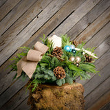 Fresh beach themed centerpiece with a burlap bow and a white pillar candle on a tree stump in front of wooden wall