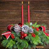 Evergreen centerpiece with white pine cones, red berries and red ball clusters, 2 white trimmed red bows & two red tapers