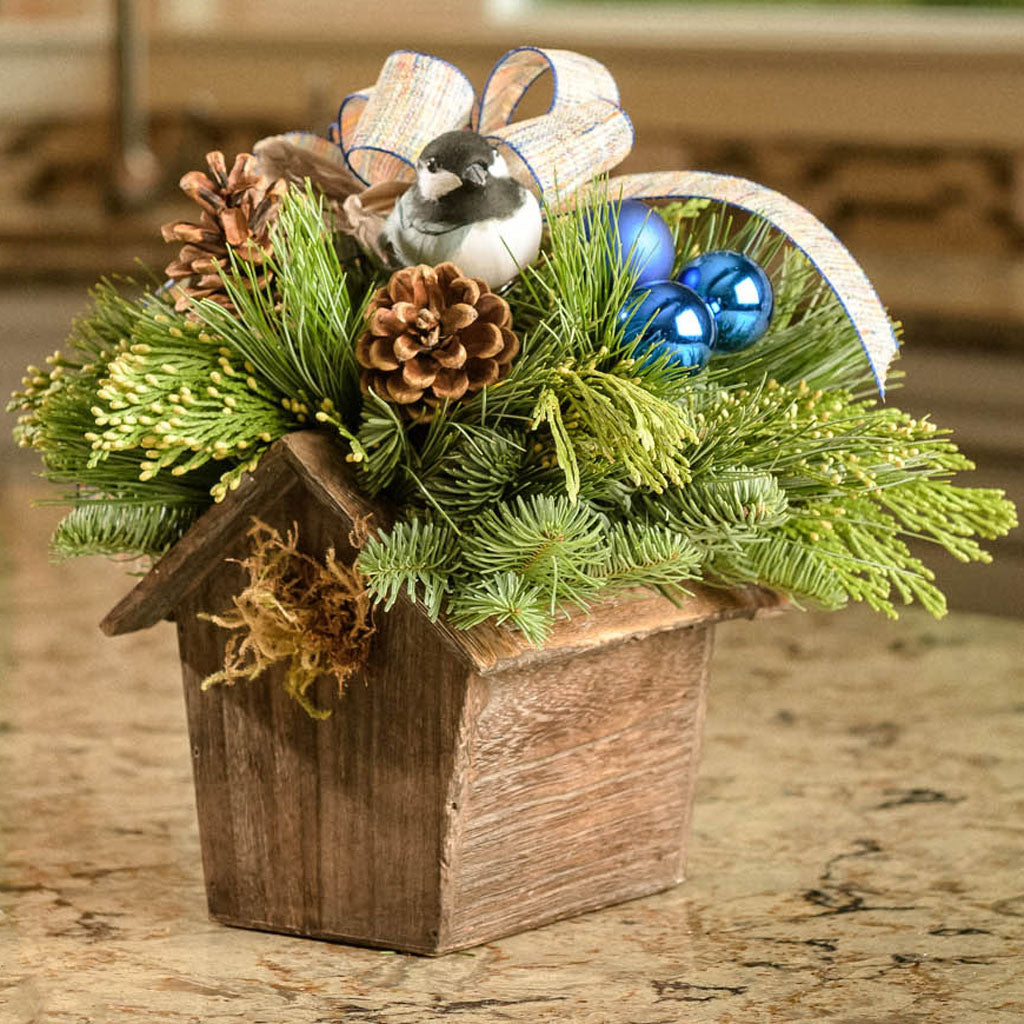 Festive bird house centerpiece with a chickadee, ornaments and a linen bow close up
