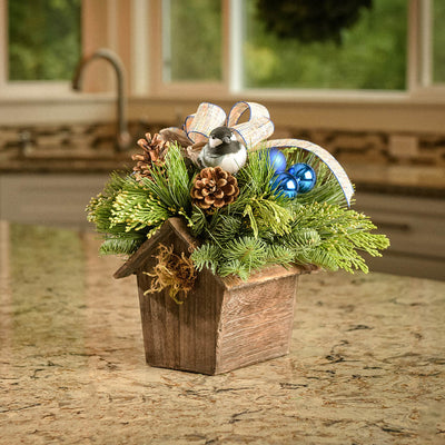 Festive birdhouse centerpiece with a chickadee, ornaments and a linen bow displayed on a kitchen counter