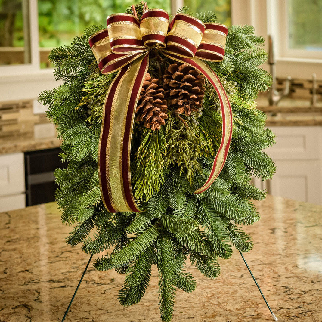 Christmas Swag made with fir cedar juniper pine cones and gold and burgundy bow