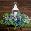 Evergreen centerpiece with white pine cones, silver and blueberries and balls, silver glitter bow and a white LED lantern