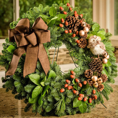 Fresh Evergreen wreath with pine cones, acorns, champagne balls, stuffed owl and brown linen bow close up