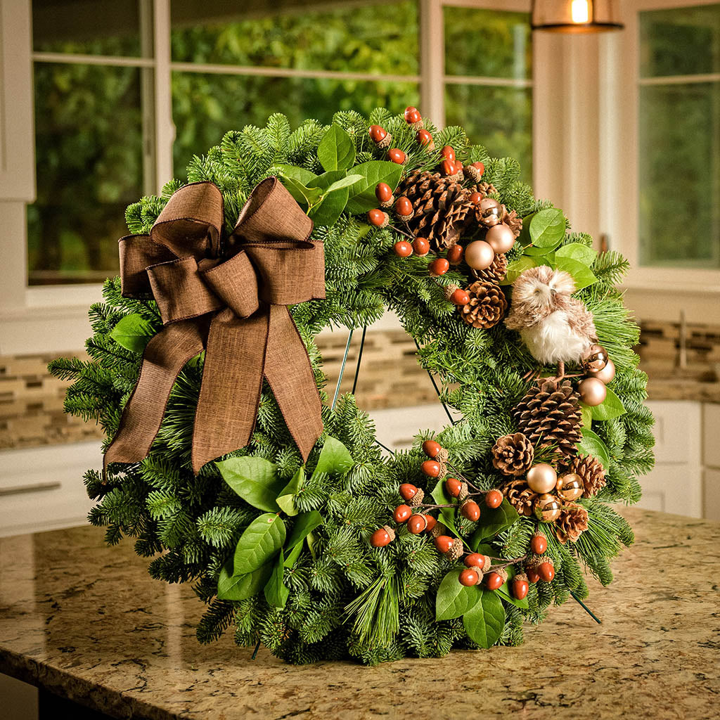 Fresh Evergreen wreath with pine cones, acorns, champagne balls, stuffed owl and brown linen bow upright on a kitchen counter