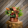 Fresh centerpiece in a bronze milk can, pine cones, holly, red balls, magnolia and a bronze bow with wooden plank background