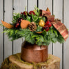 Fresh centerpiece in a bronze milk can, pine cones, holly, red balls, magnolia and a bronze bow close up on tree stump