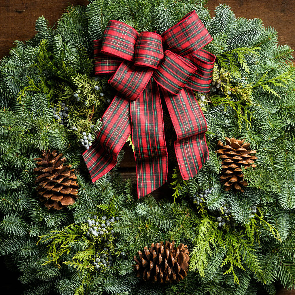 Christmas wreath of noble, cedar, juniper, pine cones and a red plaid bow close up