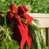 Gold backed red velveteen bow on garland on a wooden railing