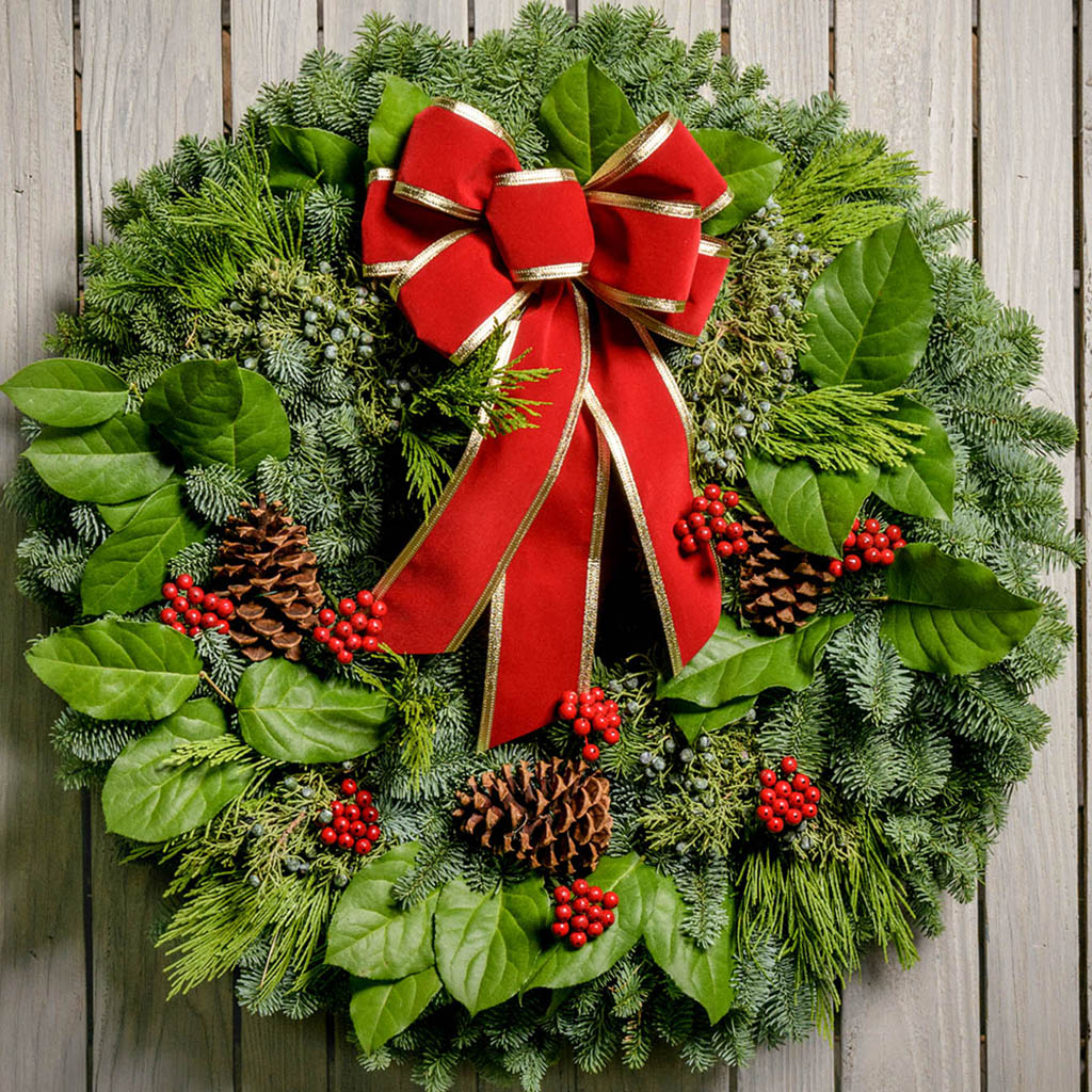 Christmas wreath of noble, cedar, juniper and salal with pine cones, red bow with gold edges and red berry clusters close up