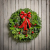 Christmas wreath with pine cones, red bow with gold edges and red berry clusters close up on wood plank background