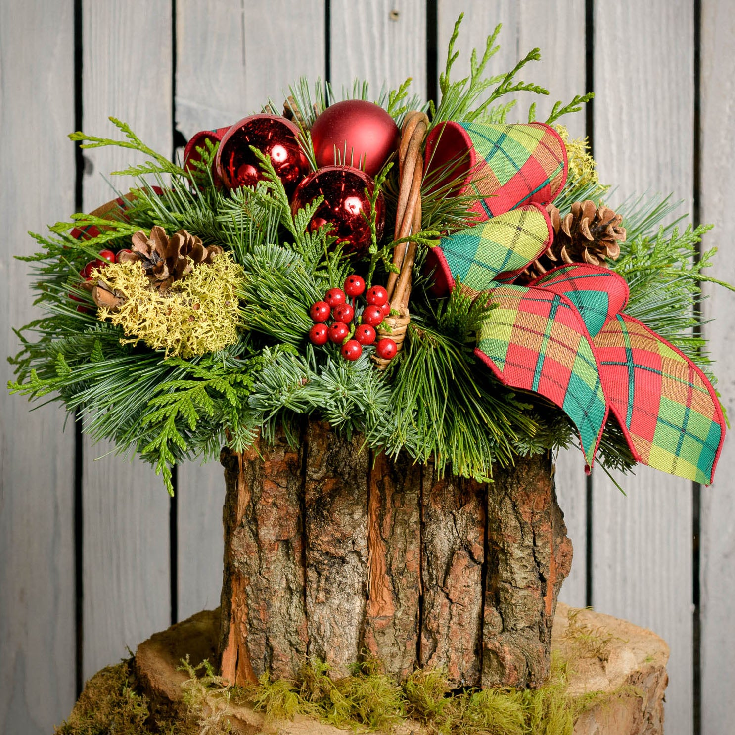 Fresh evergreen centerpiece with red ornament and berries and a plaid bow in a bark basket close up
