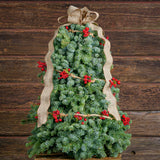 Fresh hand-assembled noble fir tree with a strand of red berry garland and natural linen wire ribbon