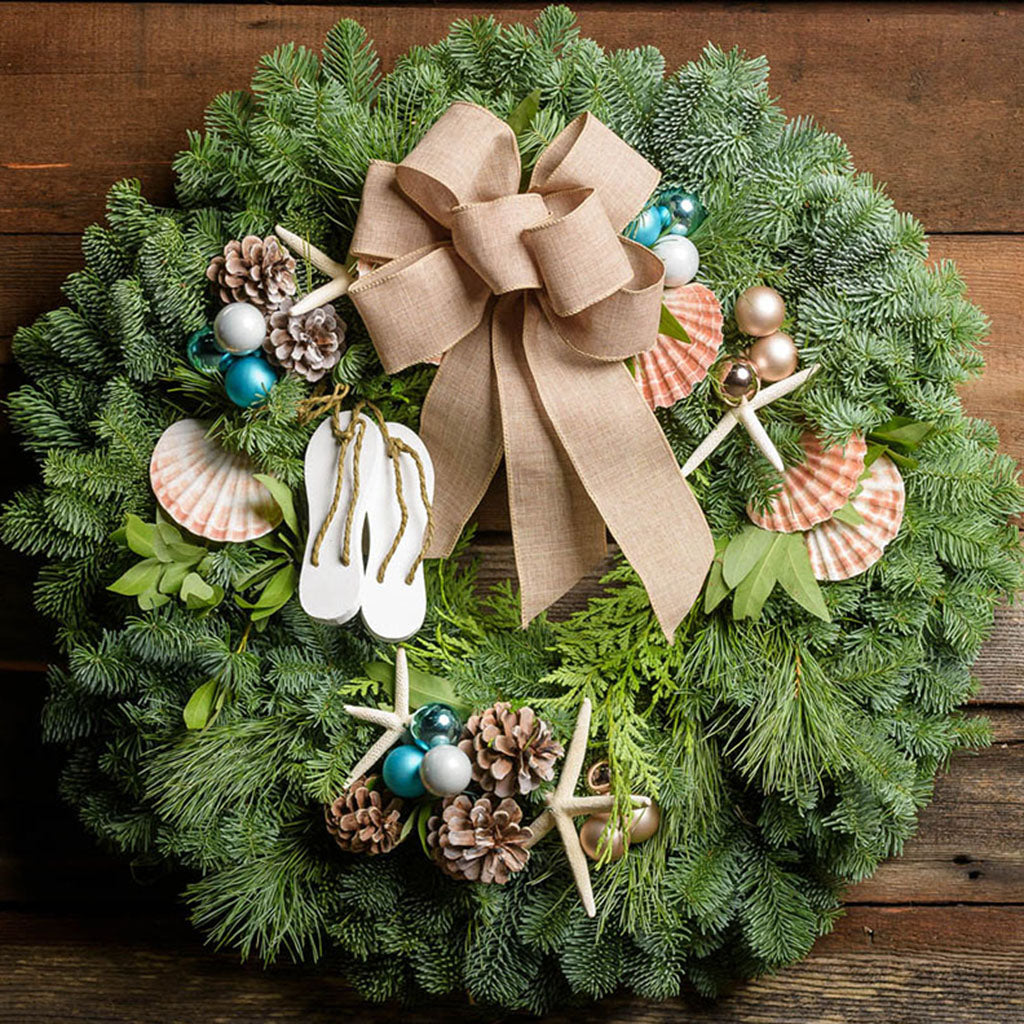 Christmas wreath with scallop shells, sea star, tiny flip flops, pine cones, aqua and white balls with a linen bow closeup