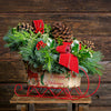 "Holiday centerpiece with pine cones, red berries, and red velvet bows in sleigh with ""happy holidays"" written on sides"