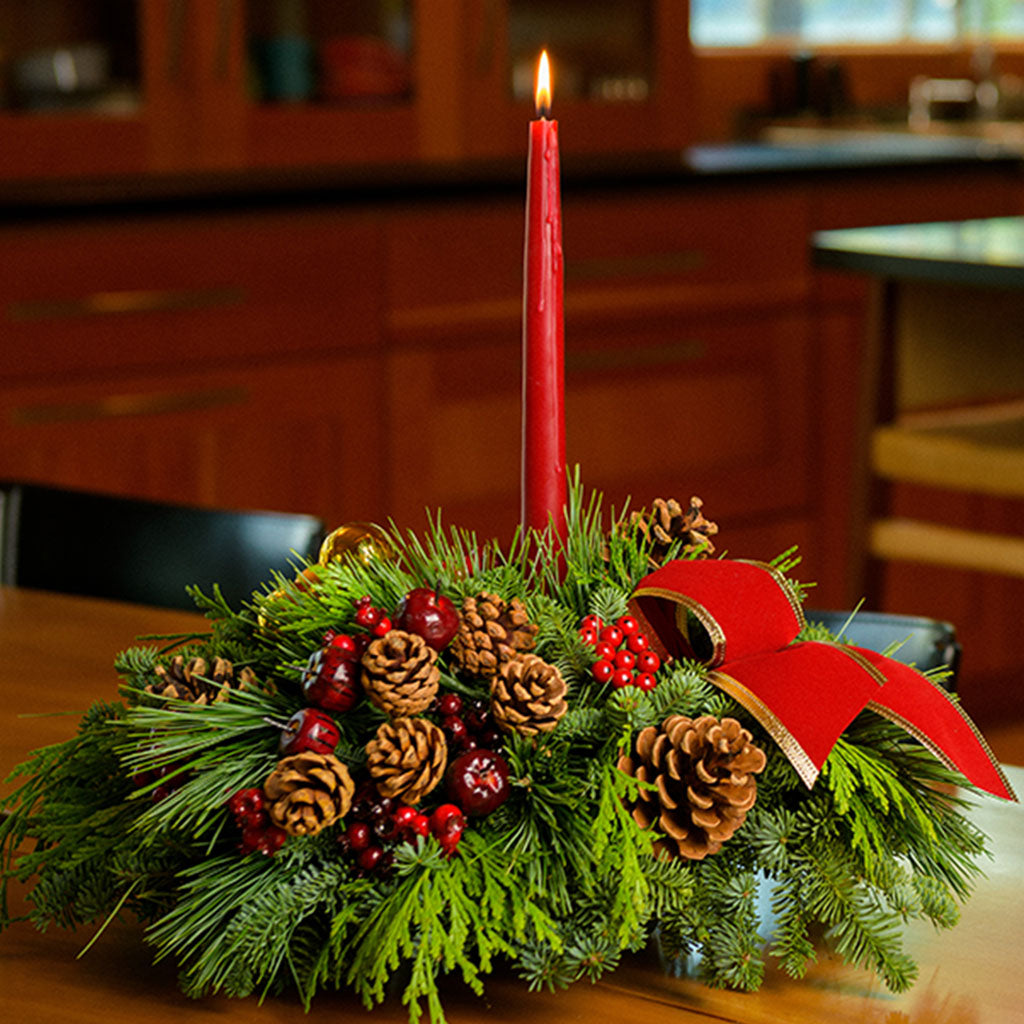 Christmas centerpiece with pine cones, gold balls and red berries with red velveteen bows and a red taper candle
