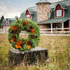 Fresh evergreen wreath made of noble fir and pine with magnolia leaves and pine cones on wooden chest in a field