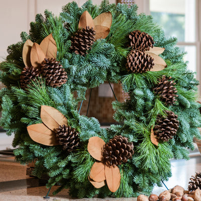 Fresh evergreen wreath made of noble fir and pine with magnolia leaves and pine cones on kitchen counter
