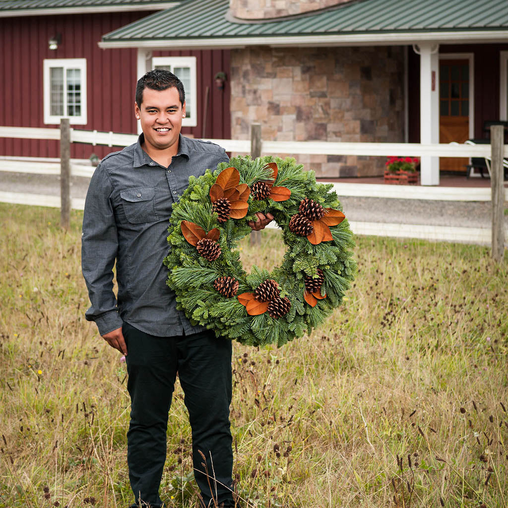 Fresh evergreen wreath made of noble fir and pine with magnolia leaves and pine cones held by man