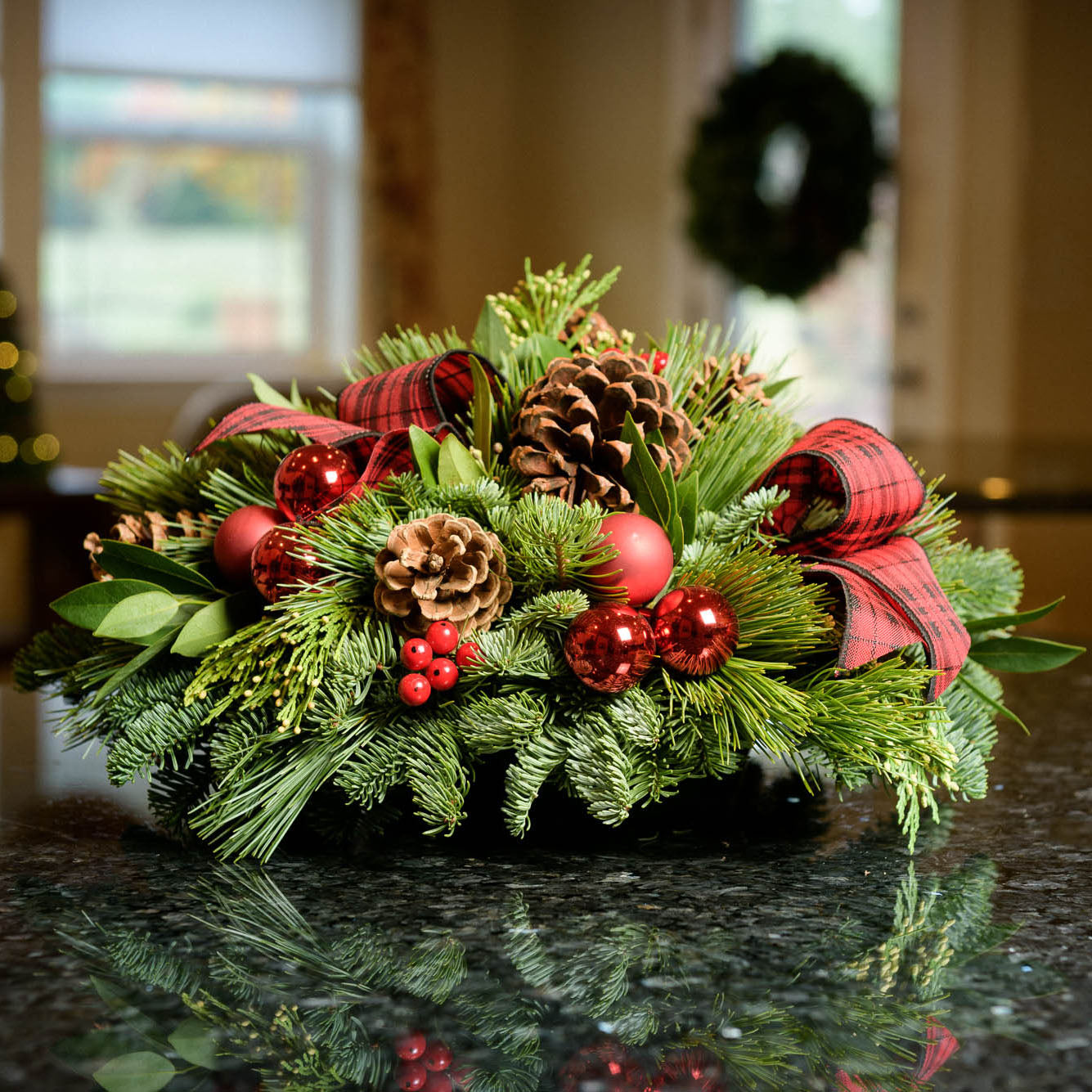 Holiday centerpiece with pine cones, red balls and red and black tartan bows sitting on a kitchen counter