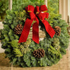 Christmas wreath made of fir, pine, cedar and juniper with pine cones and a gold-backed red velveteen bow