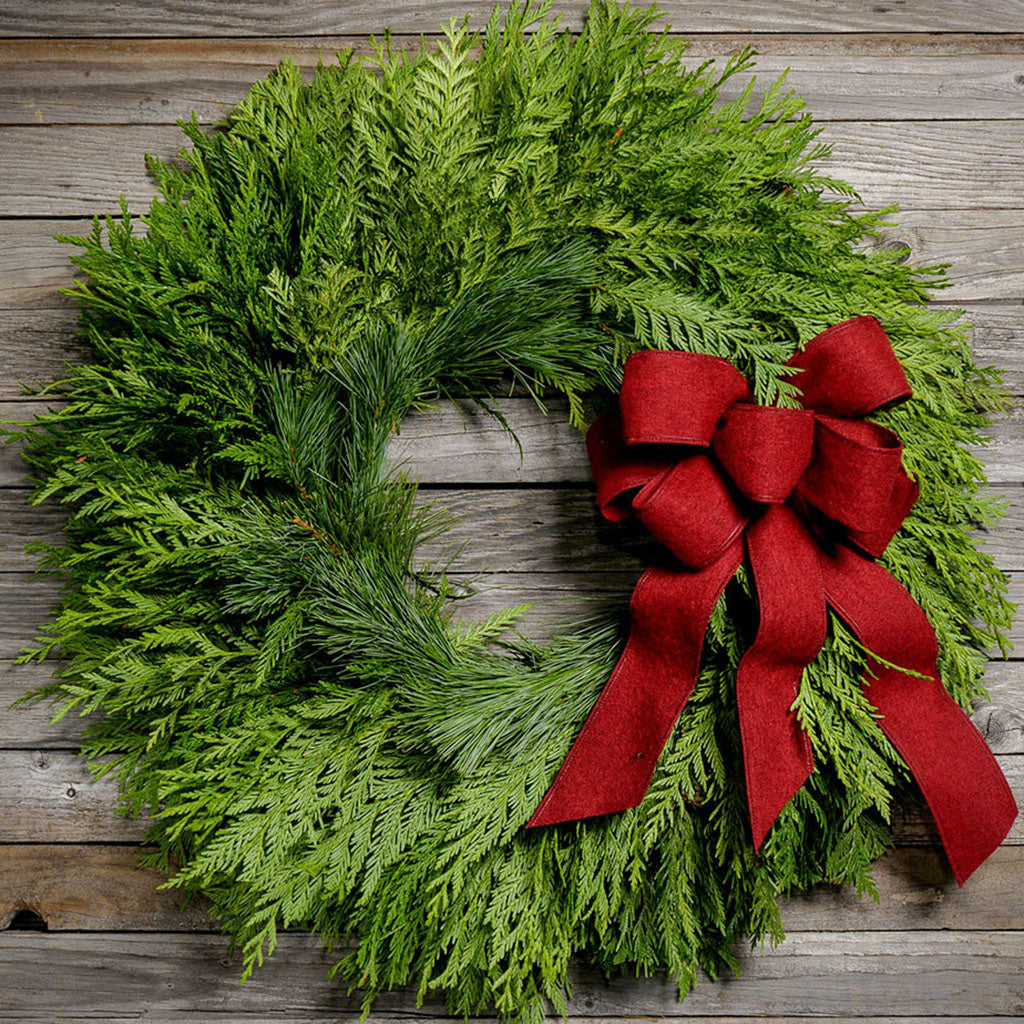 Christmas wreath with cedar and pine deep red bow on wooden background