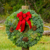 Christmas wreath made of fir, pine, cedar and juniper with pine cones and a gold-backed red velveteen bow on wood post