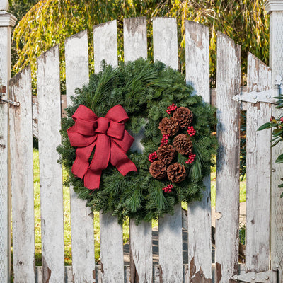 Fresh Evergreen wreath with pine cones, red berry clusters, and a wine red burlap bow on a whitewashed fence door
