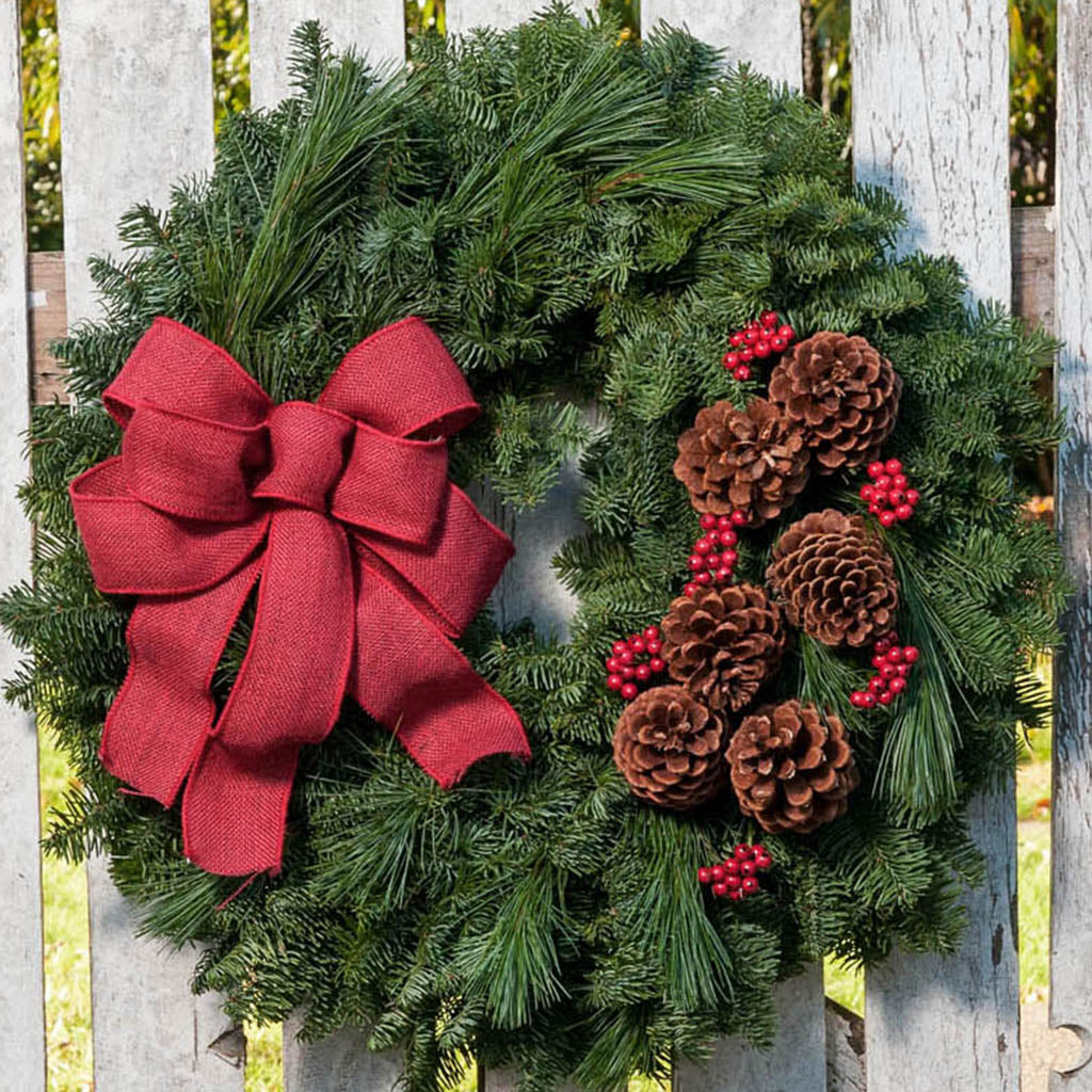 Fresh Evergreen wreath with pine cones, red berry clusters, and a wine red burlap bow on a whitewashed fence