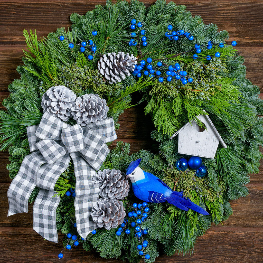 Winter themed wreath with blue jay, blue berries, silver cones, white bird house, and a white and grey gingham bow