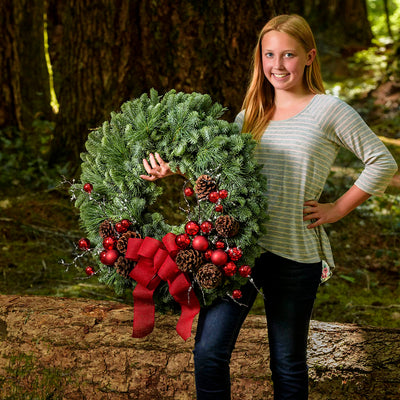 Christmas wreath held by girl pine cones red ball clusters branches lightly dusted touch of frost red globes and red bow